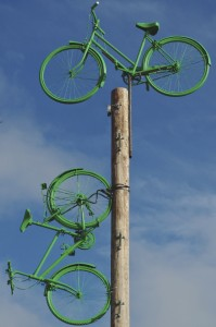 Two green bikes fixed to a disused telegraph pole.  One sits on top of the pole and the other 'cycles' down it