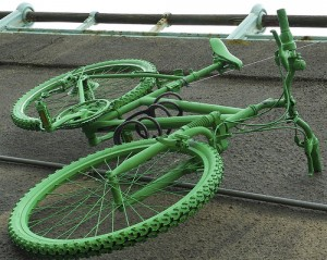 A green painted bike hangs over the railings against Brighton seafront's cliff wall
